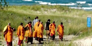 Monks-walking-over-dune-to-beach-2014
